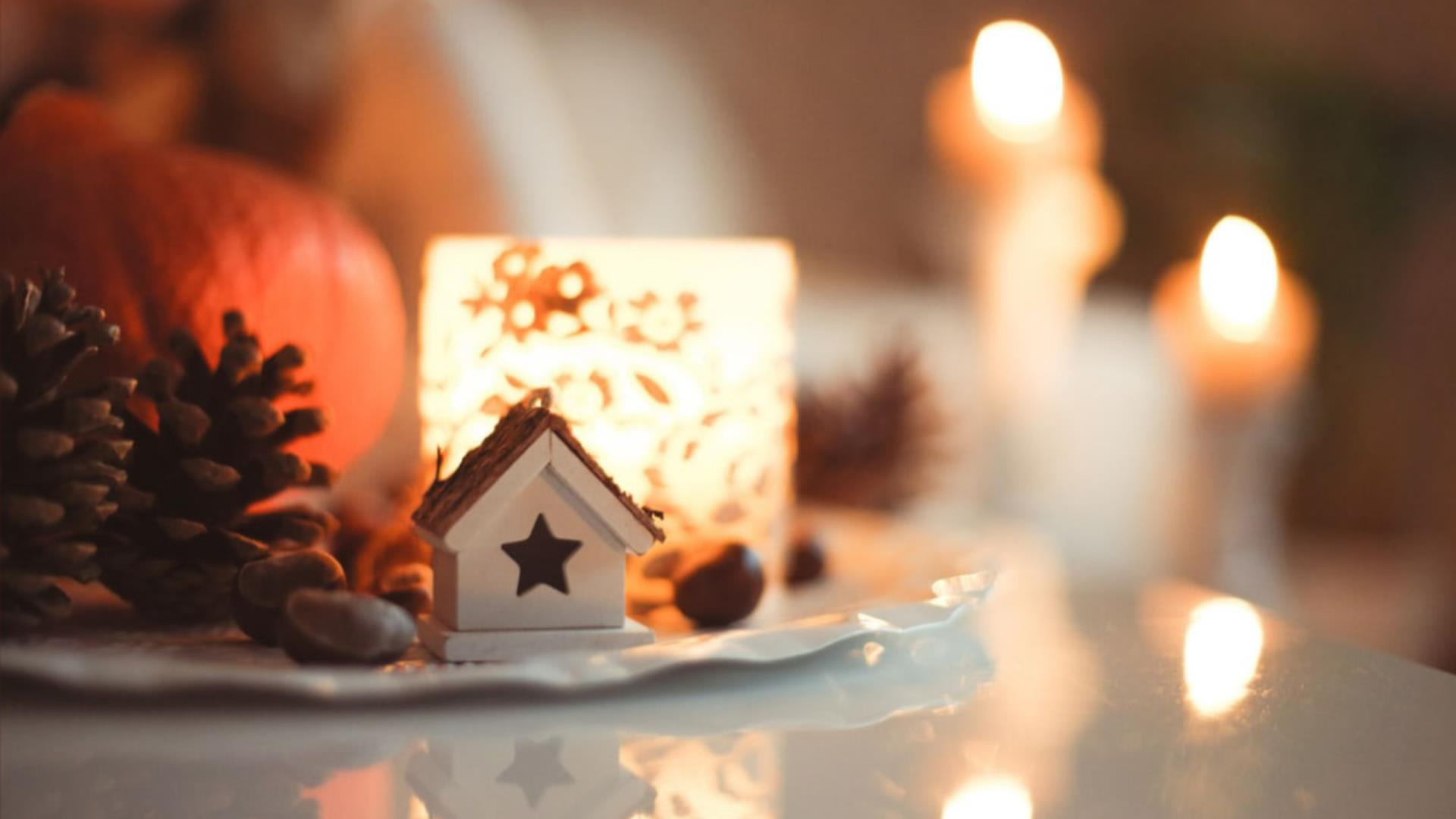 Pinecone pumkin candles on a plate with a small decravite wooden house for the holidays.